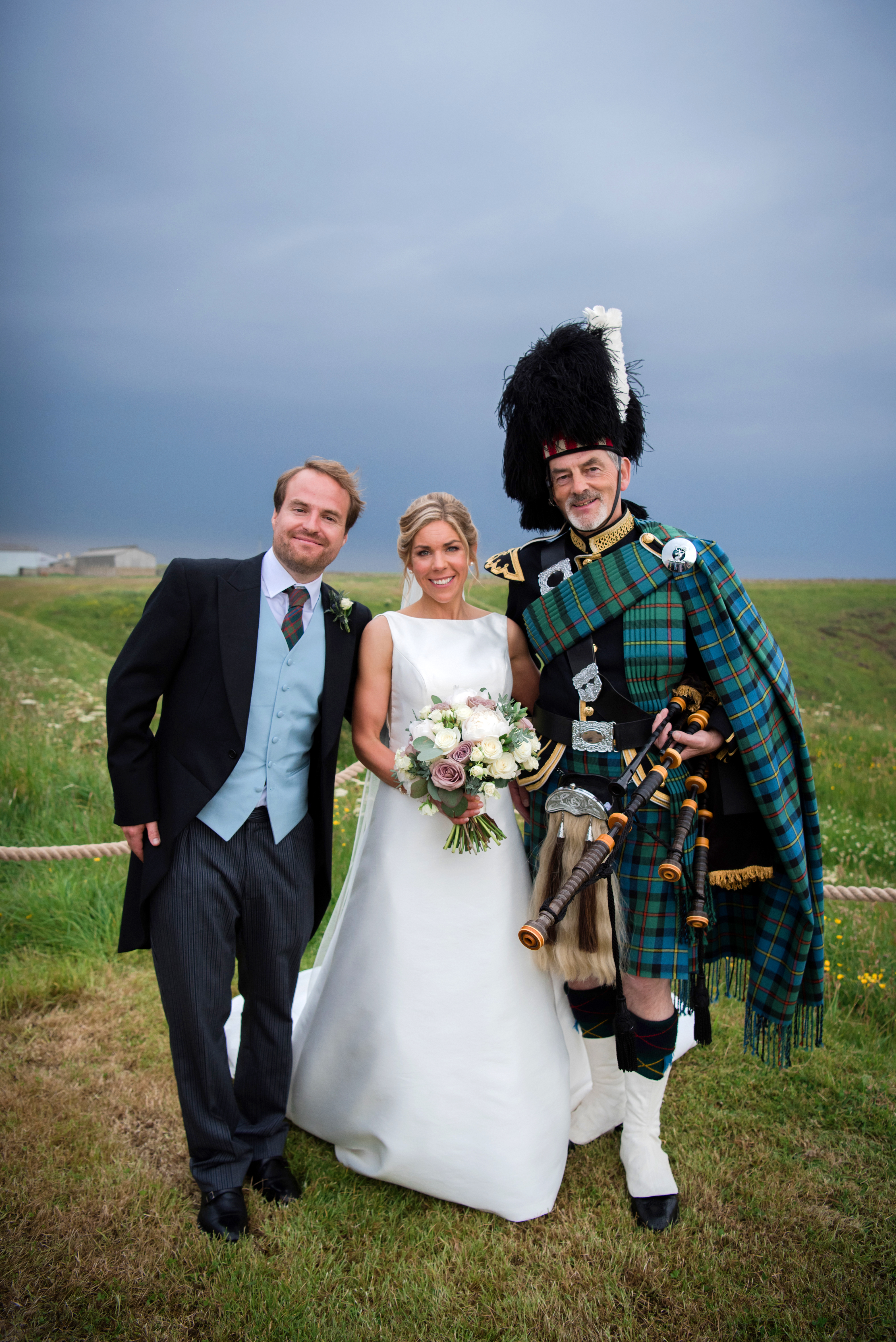 Wedding couple with Highland piper